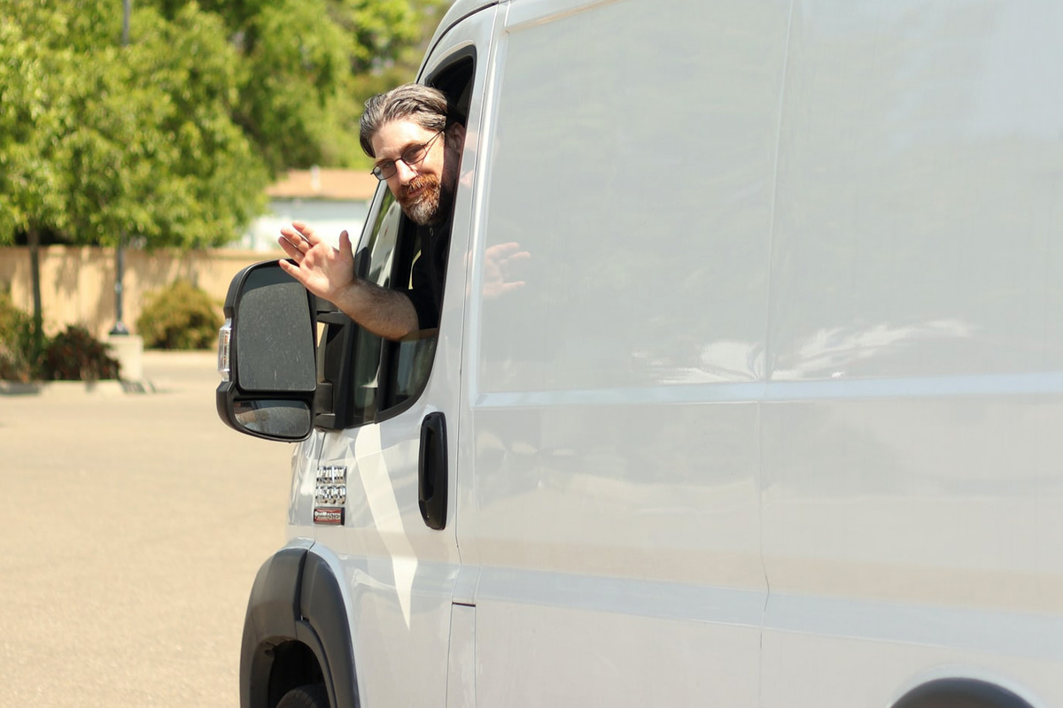 Self Furniture Removals - image showing man waving from a rental vehicle
